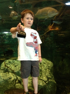 Declan with a cowbell looking like a low-class Paul Revere about to be snack for that giant River Monster behind him.